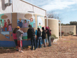 Students painting water cycle on one of the tanks. The organic garden is in the background.