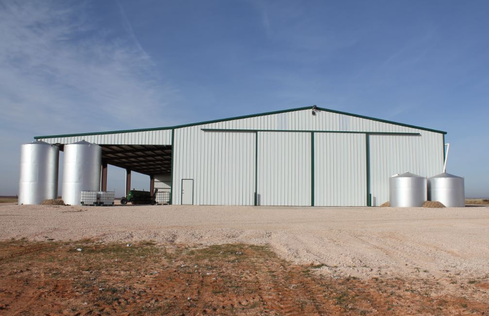 View of barn and four storage tanks.