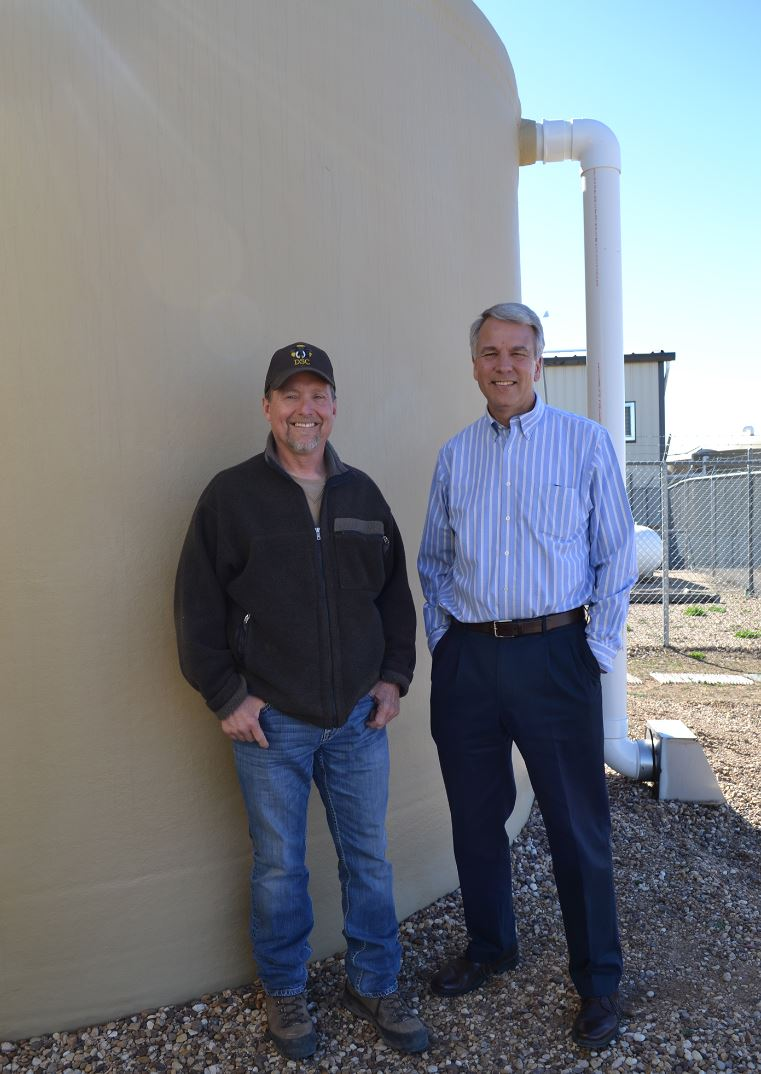 Installer Mark Fullingim and owner Chris Jackson standing near one tank.